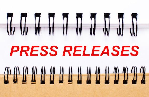 Текст пресс-релиза на белой бумаге между белыми и коричневыми спиральными блокнотами.