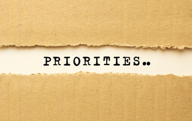 Текст приоритеты появляется за рваной коричневой бумагой. вид сверху.