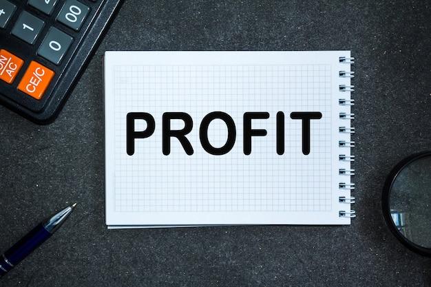 Текст profit. офисный стол, калькулятор, блокнот с документами. бизнес-концепция