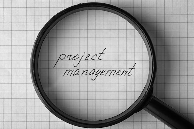 紙のシートの背景に拡大鏡の下でプロジェクト管理をテキスト