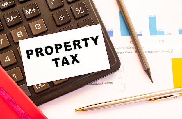 金属ペンで白いカードに固定資産税をテキストで入力します。ビジネスと財務の概念