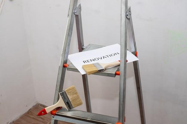 Ремонт текста, черные буквы на белой бумаге. обустройство дома, грязная лестница для краски, валик, кисть и лоток. комната для ремонта. стремянка и различные инструменты в комнате. ремонт интерьера
