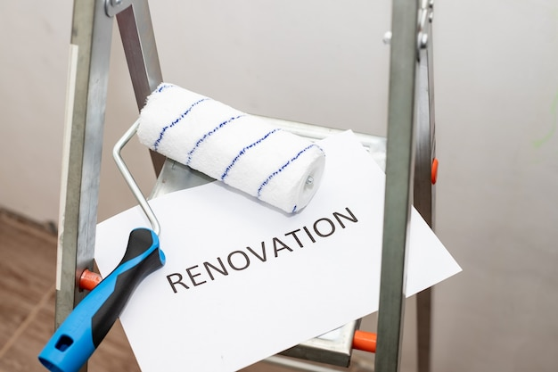 Text renovation, black letters on white paper. home improvement, dirty paint ladder, roller, brush and tray.repairing room.stepladder and different tools in room. interior renovation