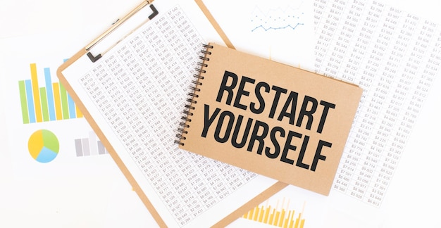 Text restart yourself on brown paper notepad on the table with diagram.
