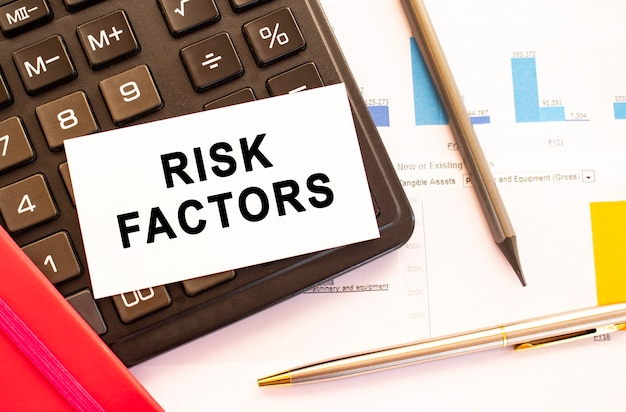 금속 펜, 계산기 및 금융 차트와 흰색 카드에 텍스트 위험 요소. 비즈니스 및 금융 개념