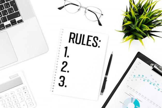 ノートブックにルールをテキストで送信します。ノートパソコン、電卓、チャート用クリップボード、メガネ、ペン、植物。フラットレイ、ビジネスコンセプト。