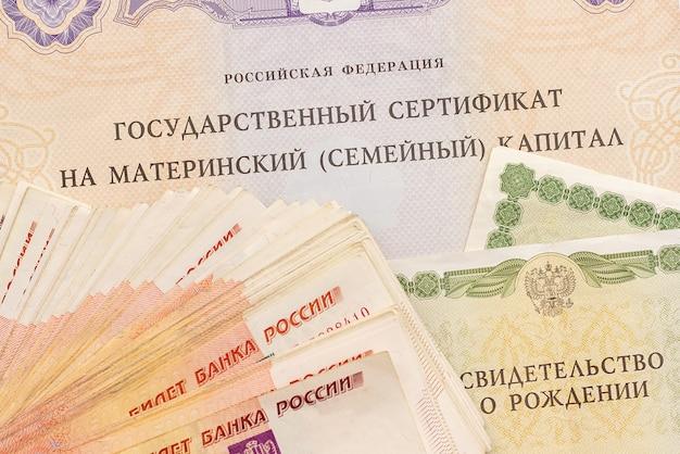 Текст российской федерации государственный сертификат на материнский семейный капитал и денежные купюры Premium Фотографии