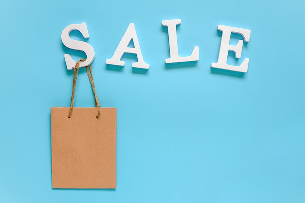 Text sale from white volume letters and blank paper shopping bag on blue .