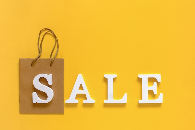 Text sale from white volume letters and blank shopping bag on yellow background.