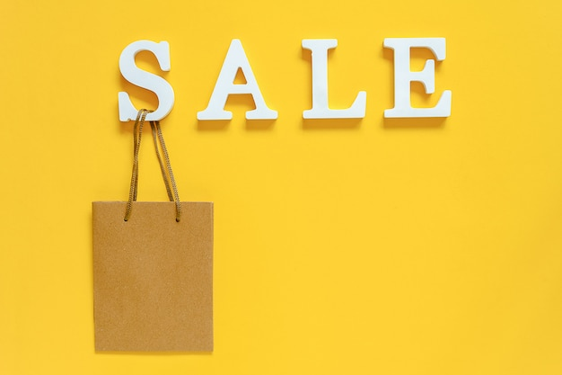 Text sale from white volume letters and blank shopping bag