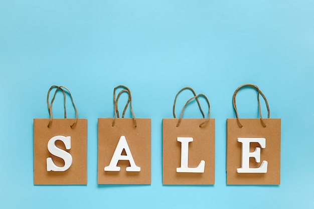 Text sale from white volume letters and blank shopping bags on blue background.
