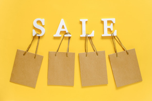 Text sale from white volume letters and blank shopping bags. concept discount.