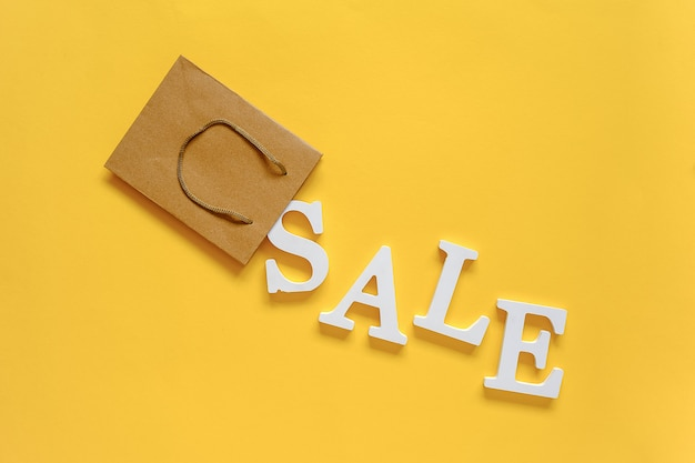 Text sale from white volume letters fall out paper shopping bag on yellow background.