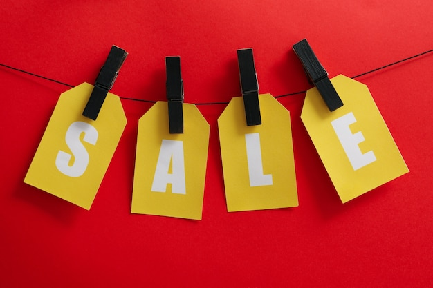 Text sale hanging on the clothesline on red