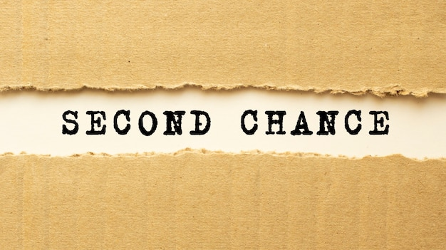 Text second chance appearing behind torn brown paper