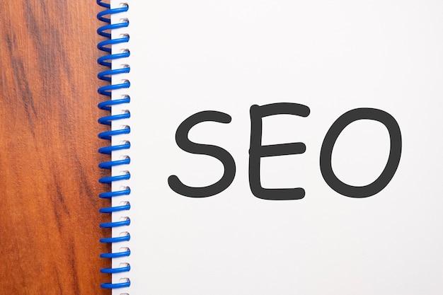 Поисковая оптимизация текста, написанная в блокноте, офисный деревянный стол сверху, концептуальное изображение для заголовка блога или изображения заголовка. выдержанный винтажный цвет.