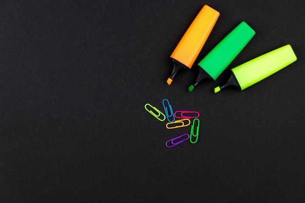 검은 색 책상에 다양한 색상의 텍스트 구분 기호와 종이 클립