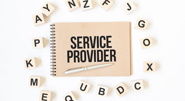 Text service provider on the craft colored notepad with block wood cubes on the white background