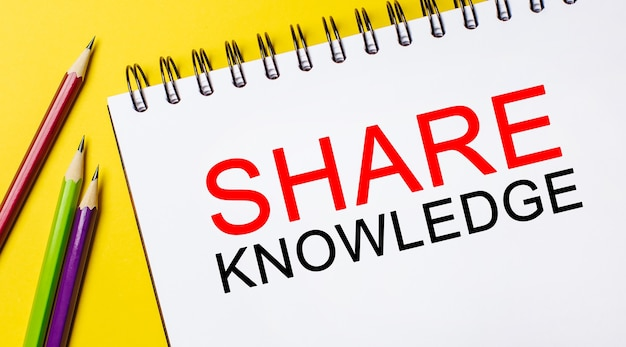 Text share knowledge on a white notepad with pencils on a yellow background.