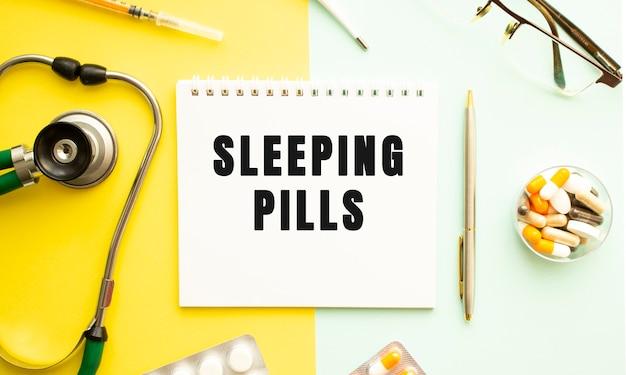 Текст сонные таблетки на ноутбуке со стетоскопом и ручкой на желтом фоне. медицинская концепция.