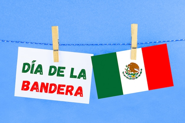 The text in spanish: the day of the flag. text with the flag of mexico.