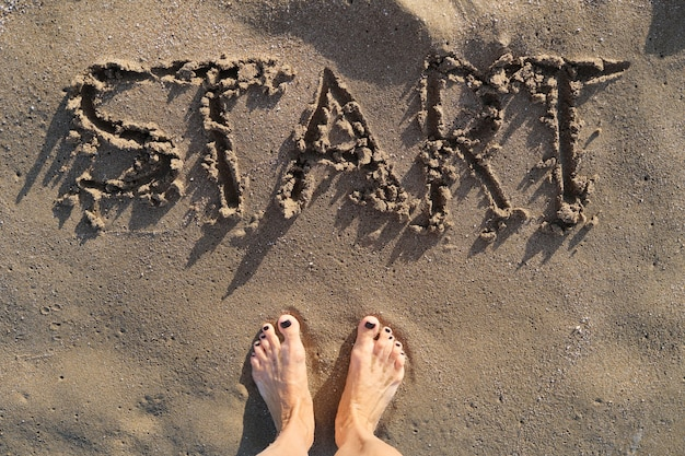 Text start written in sand on sea beach and womans bare feet standing in front of the word