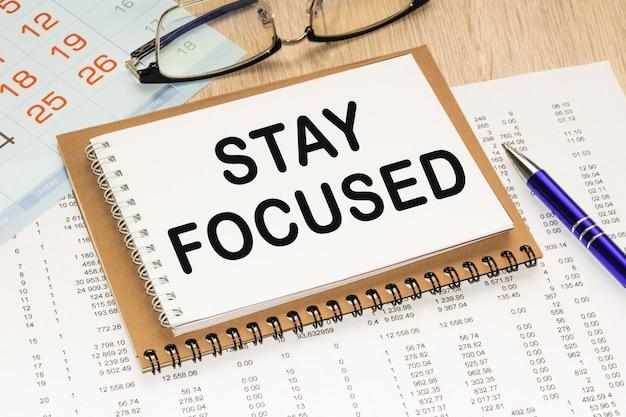 Текст оставайтесь. офисный стол, калькулятор, блокнот с документами. бизнес-концепция