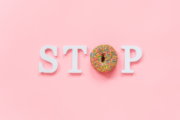 Text stop from white volume letters and glazed colorful donut diet, refusal of fast food, unhealthy food