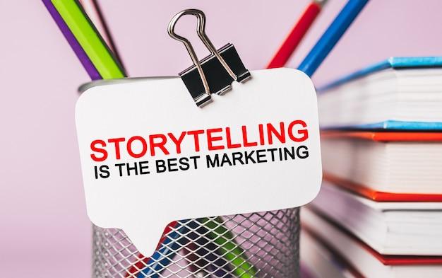 텍스트 스토리텔링은 사무용 문구 배경이 있는 흰색 스티커에 최고의 마케팅입니다. 비즈니스, 금융 및 개발 개념에 평면 누워