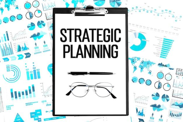 クリップボード、メガネ、グラフに戦略的計画をテキストで送信します。ビジネスコンセプト。フラットレイ。