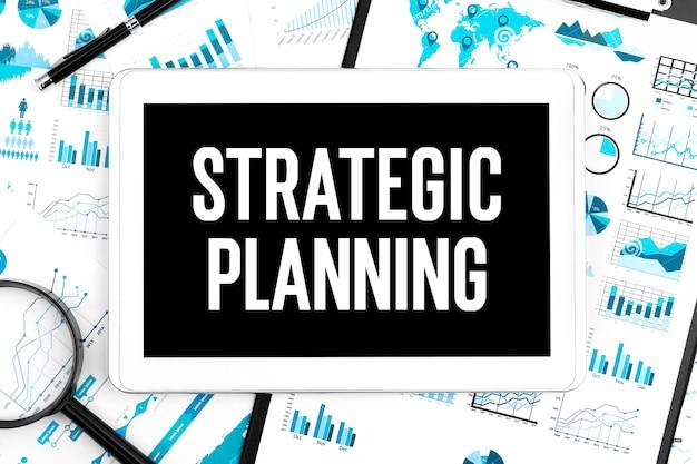 タブレット、拡大鏡、グラフに戦略的計画をテキストで送信します。ビジネスコンセプト。フラットレイ。