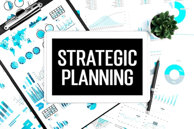 タブレットで戦略的計画をテキスト送信します。ペン、クリップボード、グラフ。ビジネスコンセプト。フラットレイ。