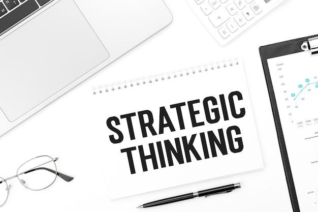 Notebokに戦略的思考をテキストで送信します。ノートパソコン、ペン、メガネ、電卓、クリップボード。ビジネスコンセプト。フラットレイ。