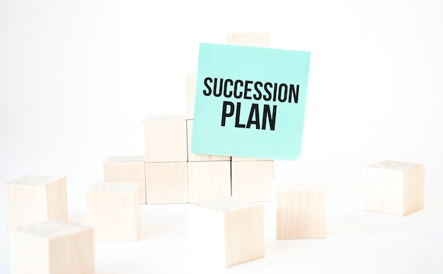 Text succession plan writing in green card cube ladder. white background. business concept