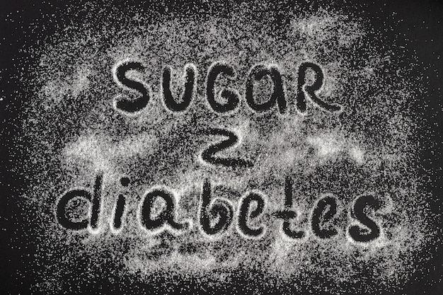Text sugar - diabetes on a scattering of sugar crystals, blac