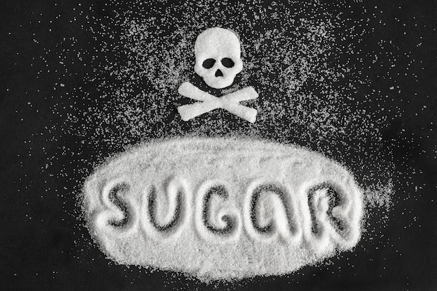 Text sugar and skull shape from sugar on black background, concept