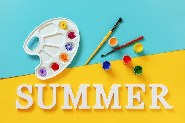 텍스트 여름, 아티스트 팔레트에 밝은 다채로운 꽃, 파란색 노란색 배경에 브러시 및 구아슈. 크리에이 티브 개념 여름 색상 페인트입니다. 디자인 엽서 초대장을 위한 평면도 템플릿입니다.