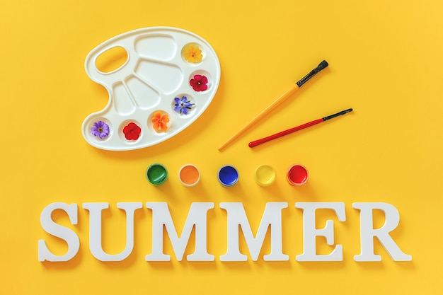 Text summer with bright colorful flowers on artistic palette, brush and gouache on yellow surface