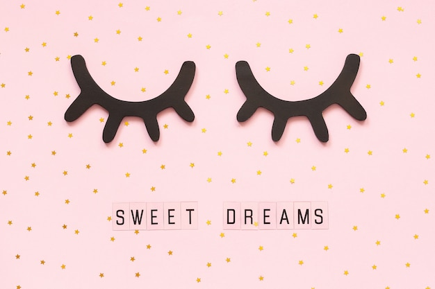 Text sweet dreams and decorative wooden black eyelashes, closed eyes gold star on pink background.