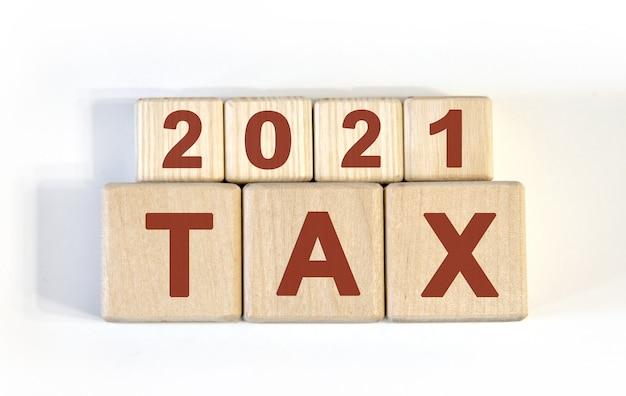 テキスト-木製の立方体、木製の背景に2021年の税金
