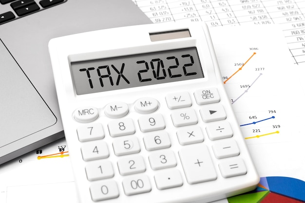 Text tax 2022. calculating machine, laptop and charts, documents and graphs top view. business and tax concept on white background.