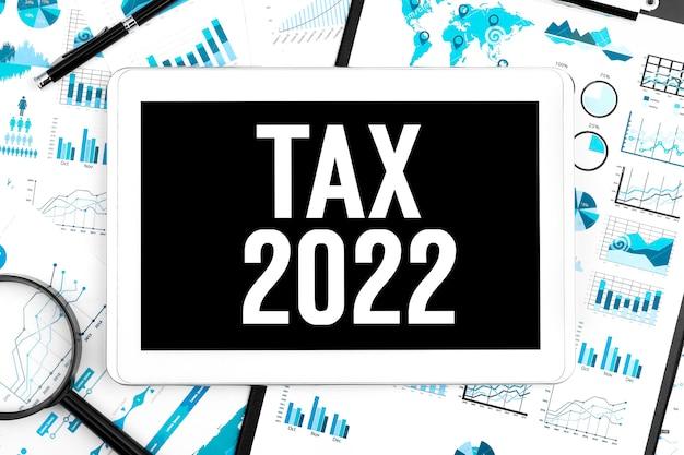 タブレットでtax2022にテキストメッセージを送信します。クリップボード、ペン、拡大鏡、チャート、ドキュメント、グラフの背景。ビジネスコンセプト。フラットレイ。