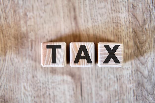テキスト-木製の立方体、木製の背景に課税