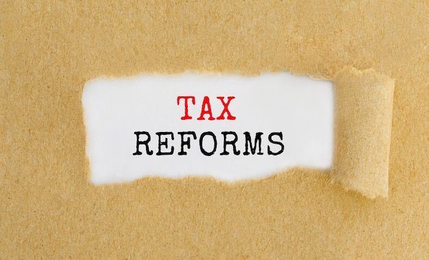 Text tax reforms appearing behind ripped brown paper.