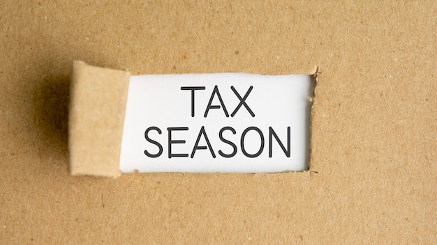 The text tax season behind torn brown paper