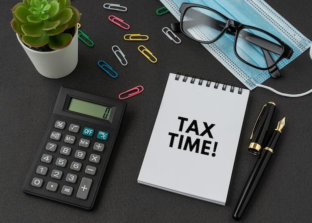 Текст «tax time» на блокноте с калькулятором, ручкой, очками и маской для лица на черной поверхности. концепция бизнеса и финансов.