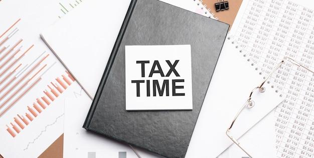 Текст налоговое время на блокноте с офисными инструментами, ручка на финансовом отчете. деловая и финансовая концепция. калькулятор и рабочий документ со схемой.