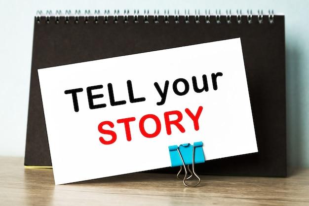 당신의 이야기를 문자로 보내세요. 책상 배경에 닫힌 검은색 커버 노트북의 상위 뷰.
