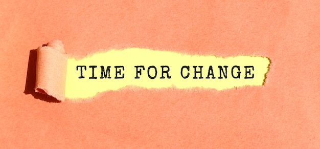 The text time for change appearing on yellow paper behind torn color paper. top view.