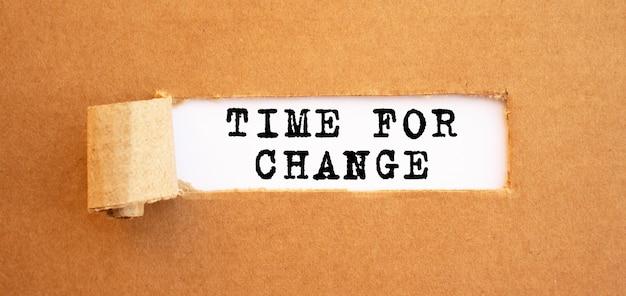 찢어진 갈색 종이 뒤에 나타나는 time for change 텍스트.